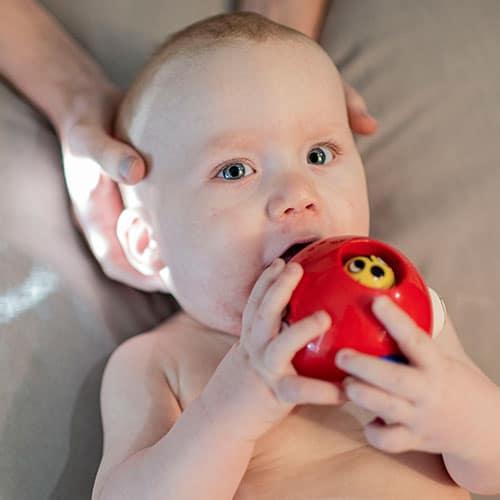 Detail osteopaat die een baby behandelt